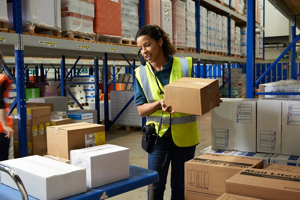 Woman working with mobile tech in warehouse